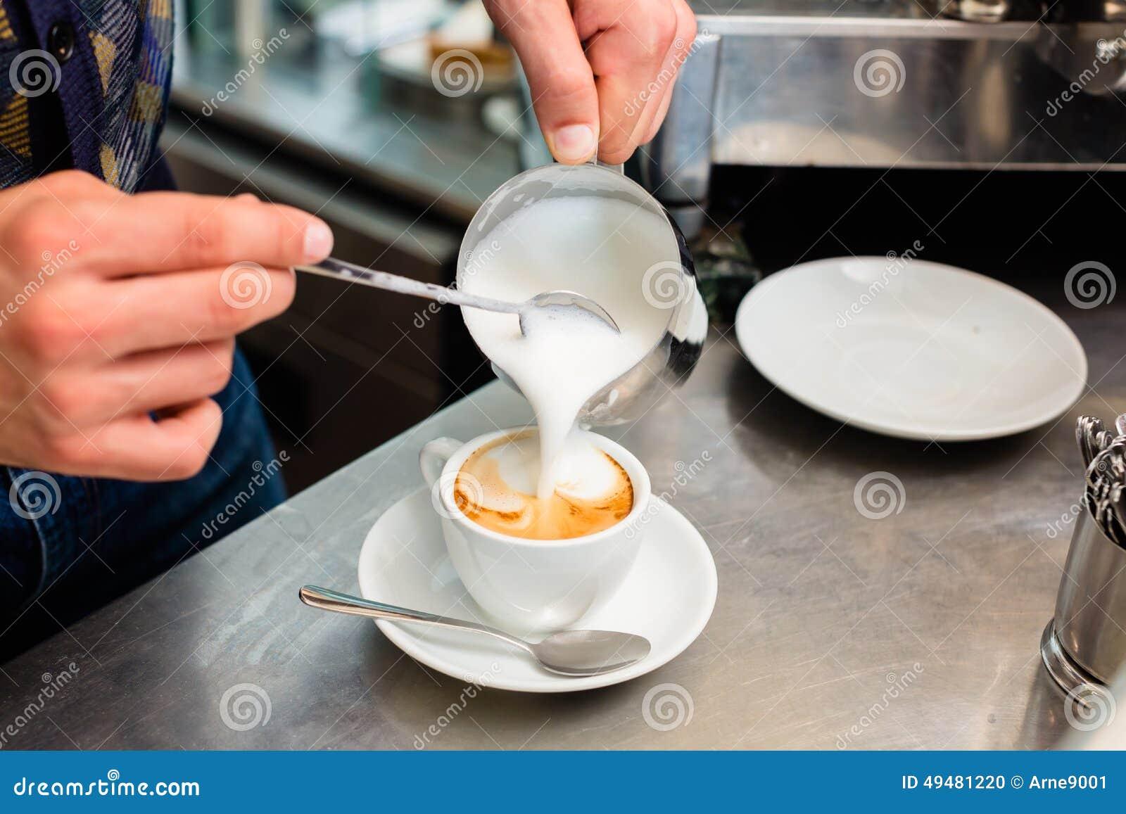 Barista en la barra del café o de café que prepara capuchino