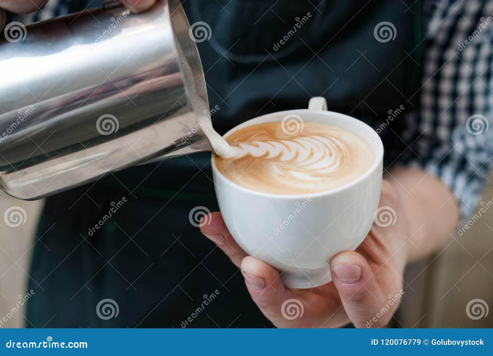Barista expertis häller mjölkar cappuccinokoppcafeterian