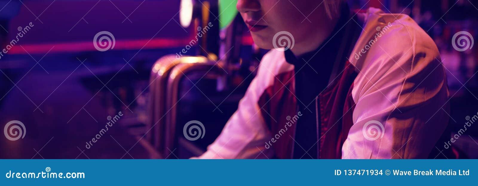 Barista femminile che per mezzo della compressa digitale al contatore della barra