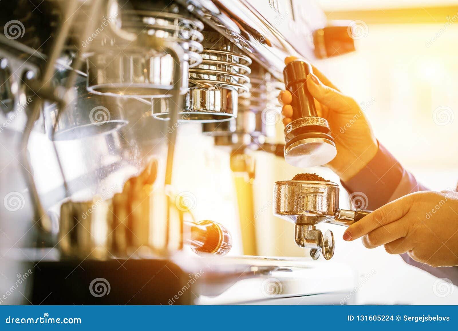 Barista gebruikend koffiemachine om koffie in de koffie te maken
