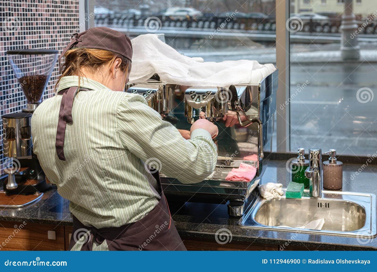 Barista-Mädchen bereitet Kaffee in der Kaffeemaschine zu