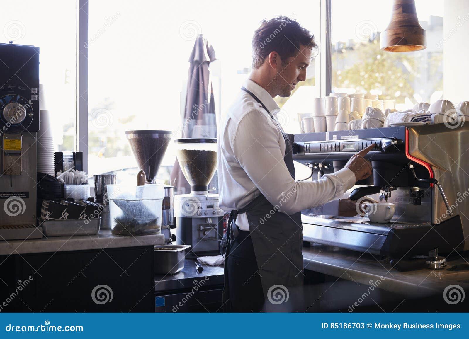 Barista Making Coffee In matvaruaffär genom att använda maskinen