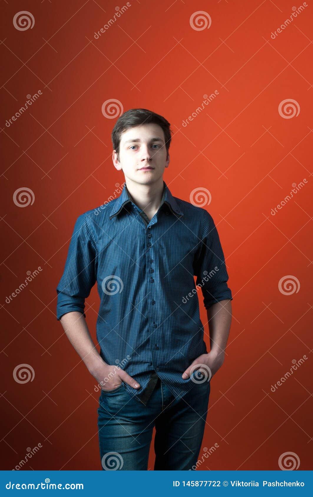 Barista na camisa azul e nas calças de brim que estão com mãos em uns bolsos e que olham a câmera no fundo alaranjado