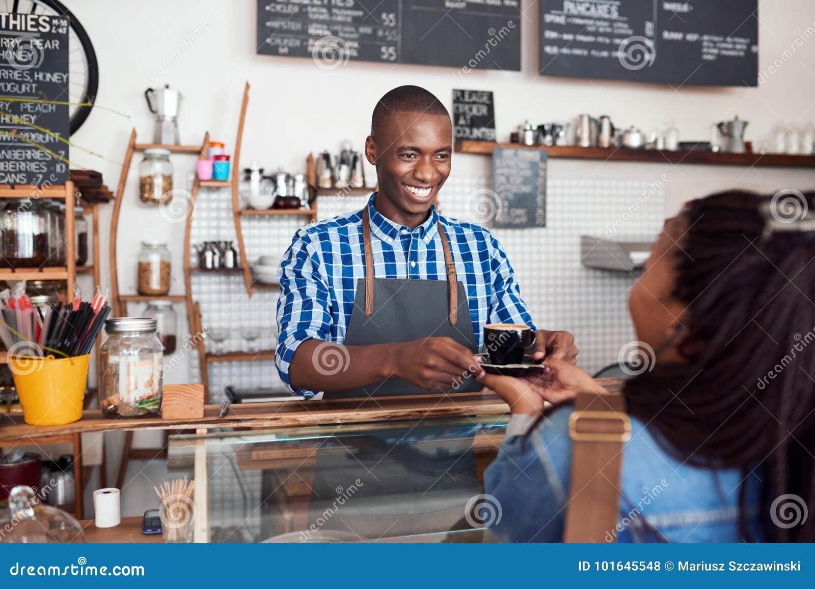 Barista novo de sorriso que entrega o café a um cliente do café