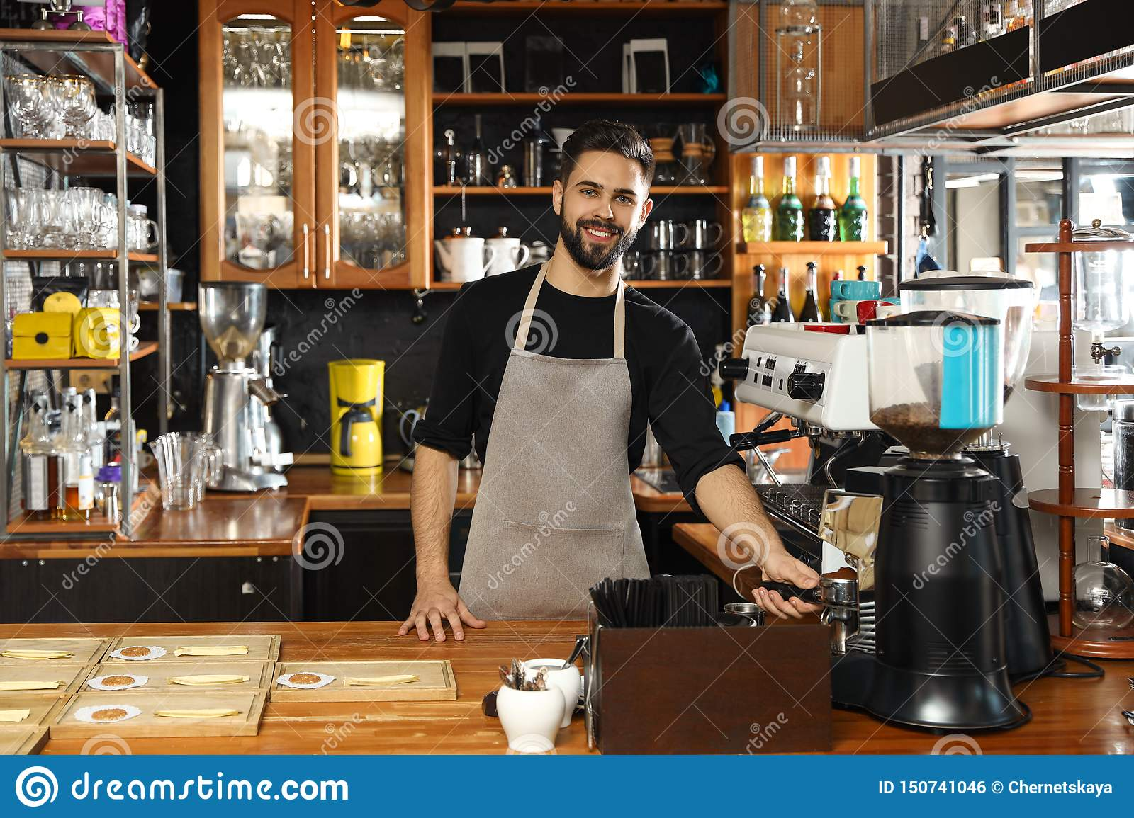 Barista pouring milled coffee from grinding machine into portafilter