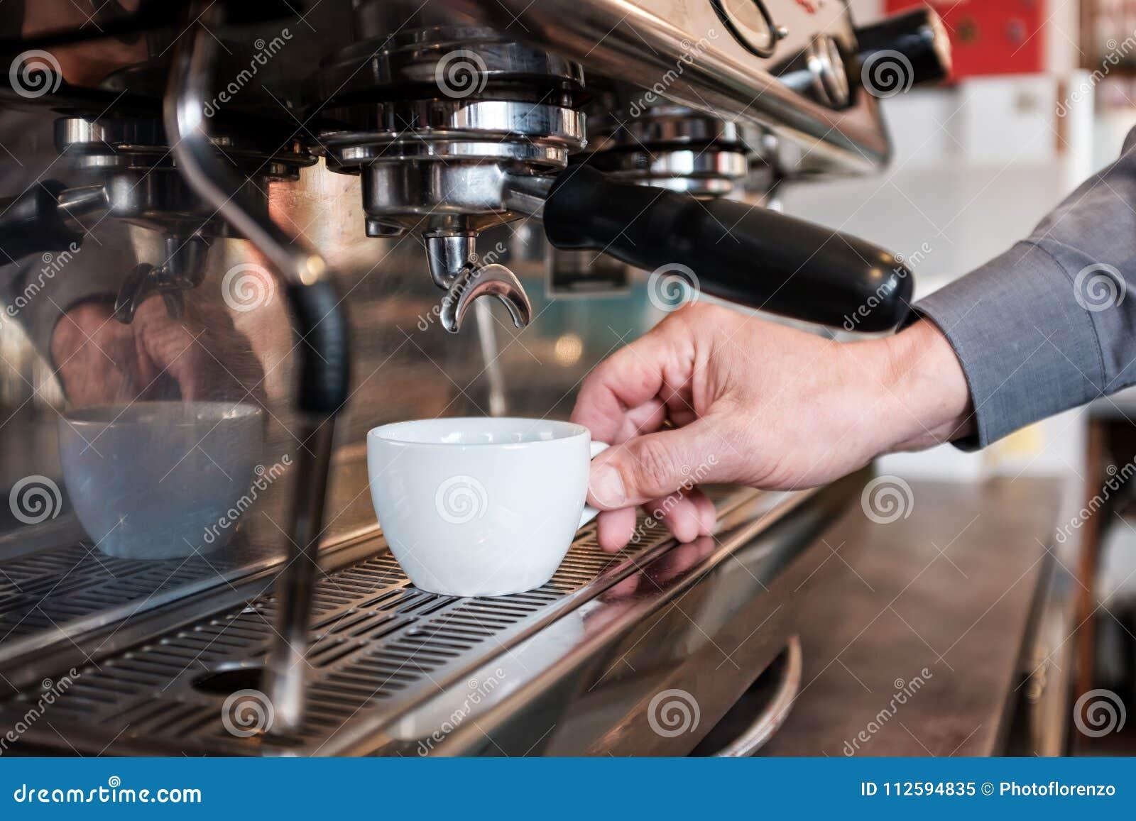 Barista que coloca o copo na máquina do café a fazer o café fresco