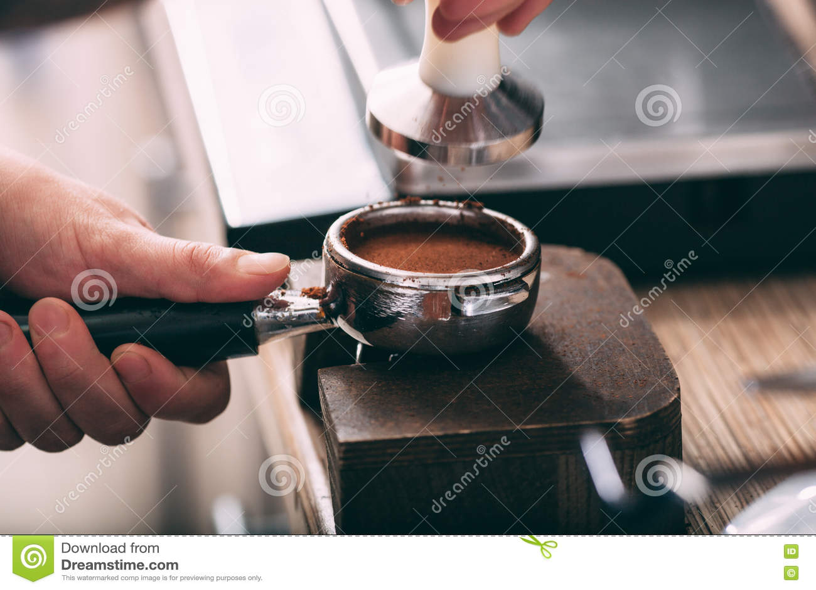 Barista que presiona el café en el tenedor de la máquina
