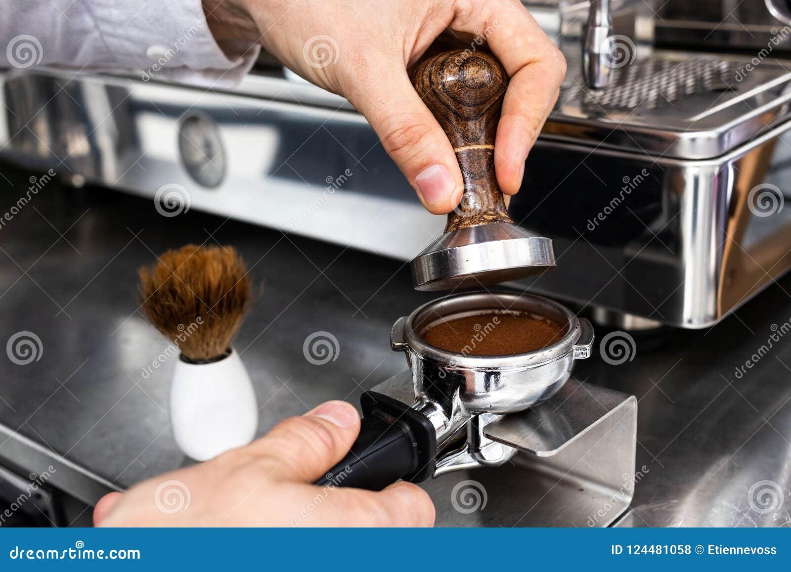 Barista que presiona el café molido en portafilter con un pisón