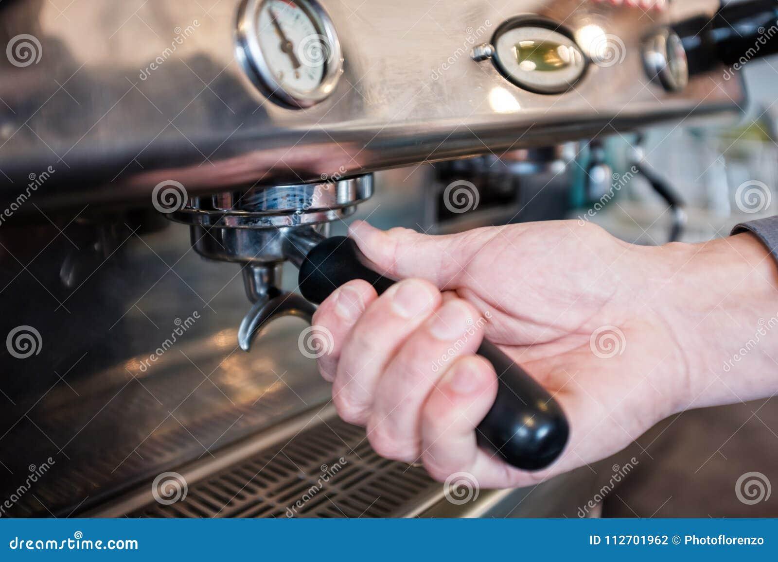 Barista que trava o portafilter com café no grouphead do café m