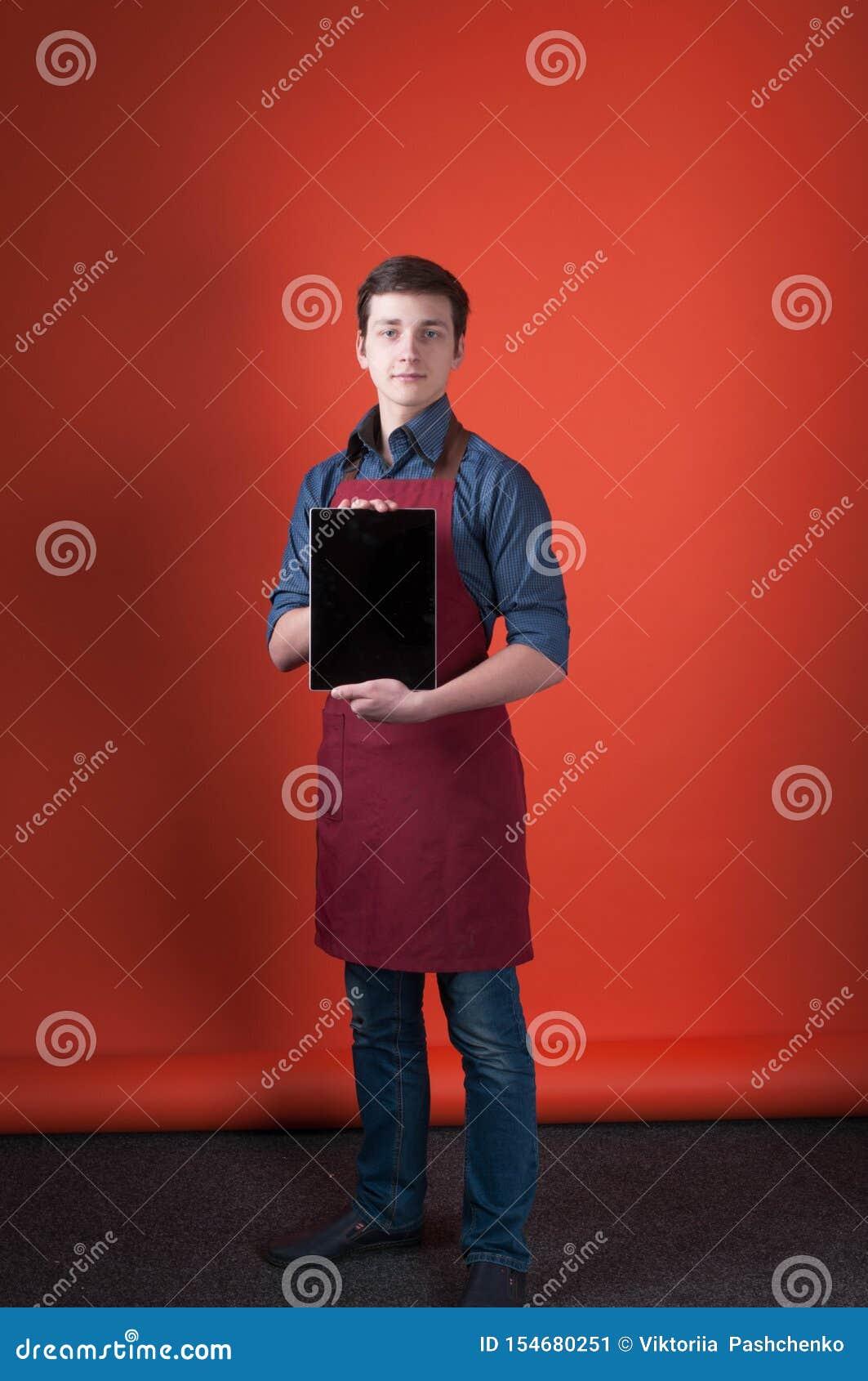 Barista z ciemnym włosy w koszula, cajgach i Burgundy fartuchu trzyma cyfrową pastylkę błękitnych,