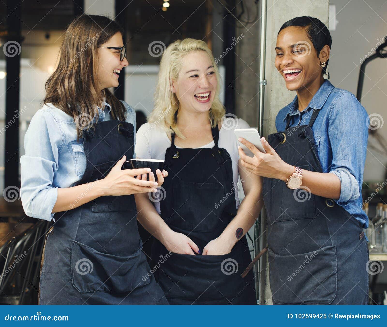 Baristas που προσέχει κάτι αστείο σε ένα τηλέφωνο