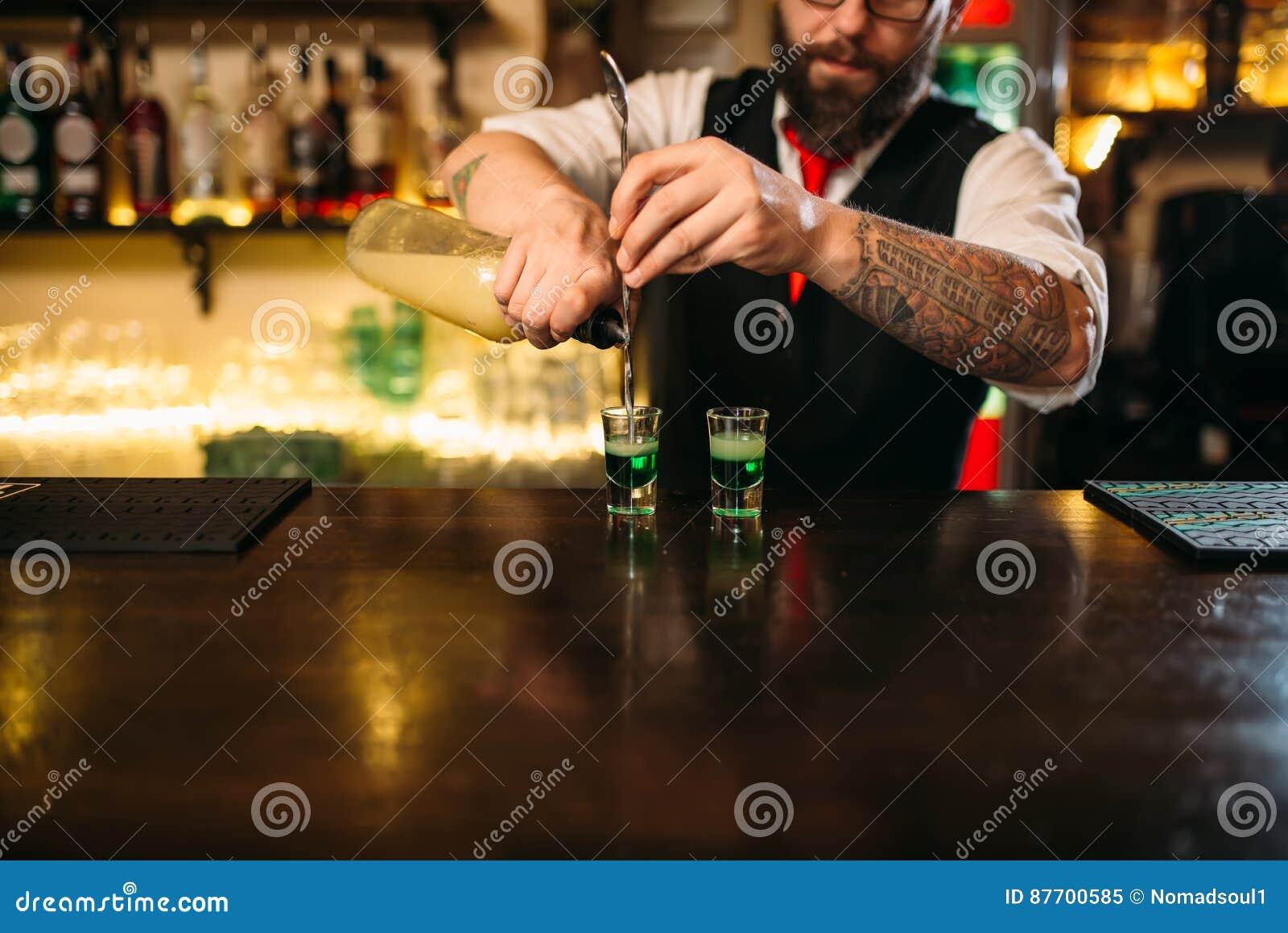 Barkeeper versant la boisson alcoolisée en verre