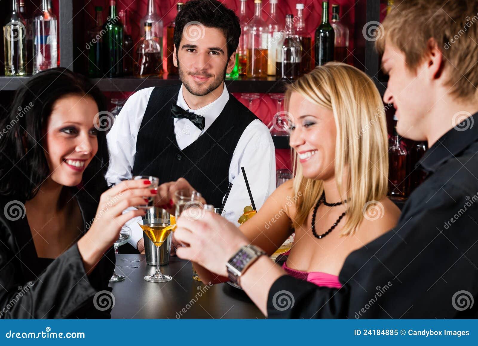 Barkellner hinter den Gegenfreunden, die am Stab trinken