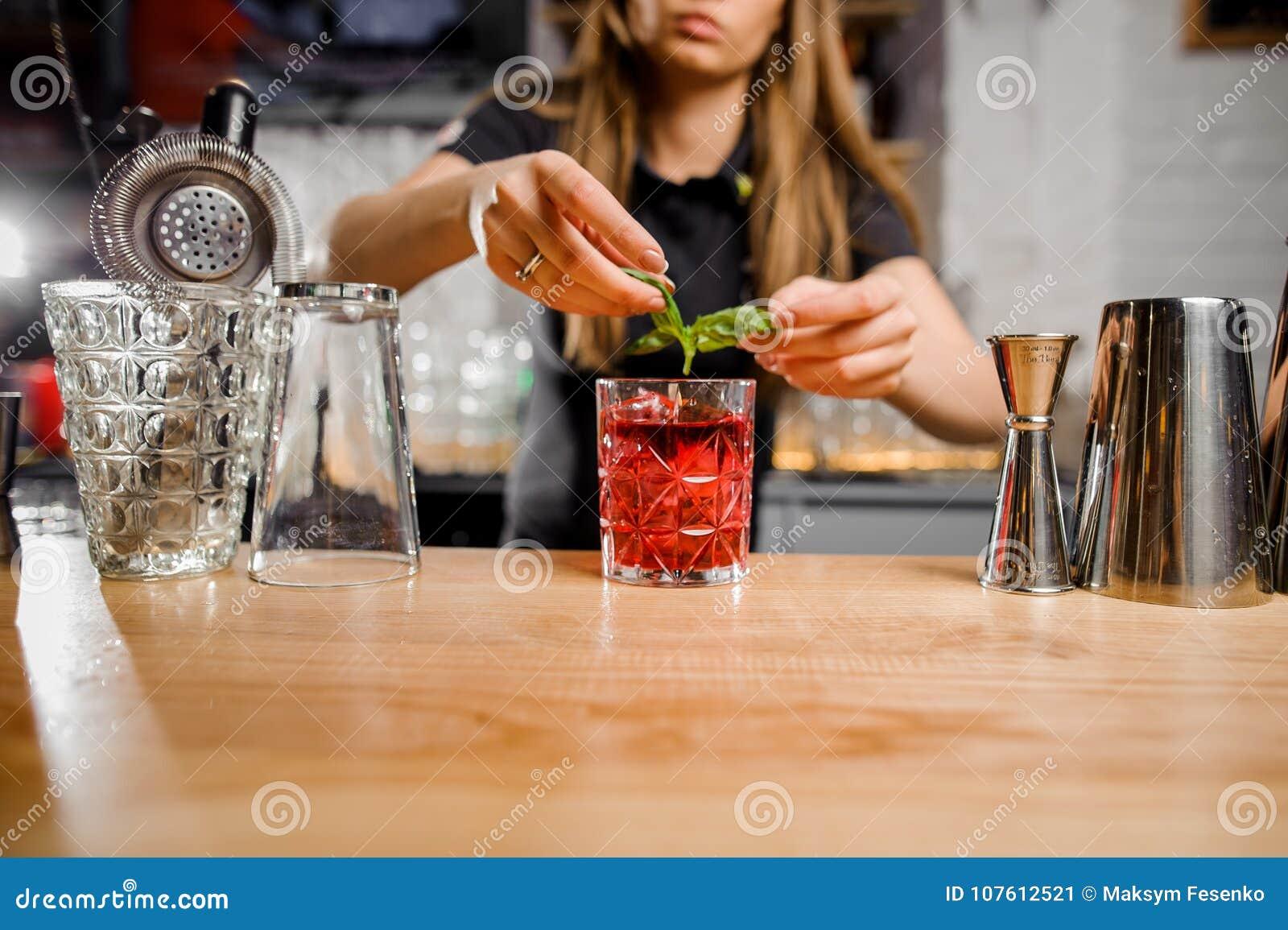 Barmaid blonde ajoutant aux feuilles en bon état de cocktail