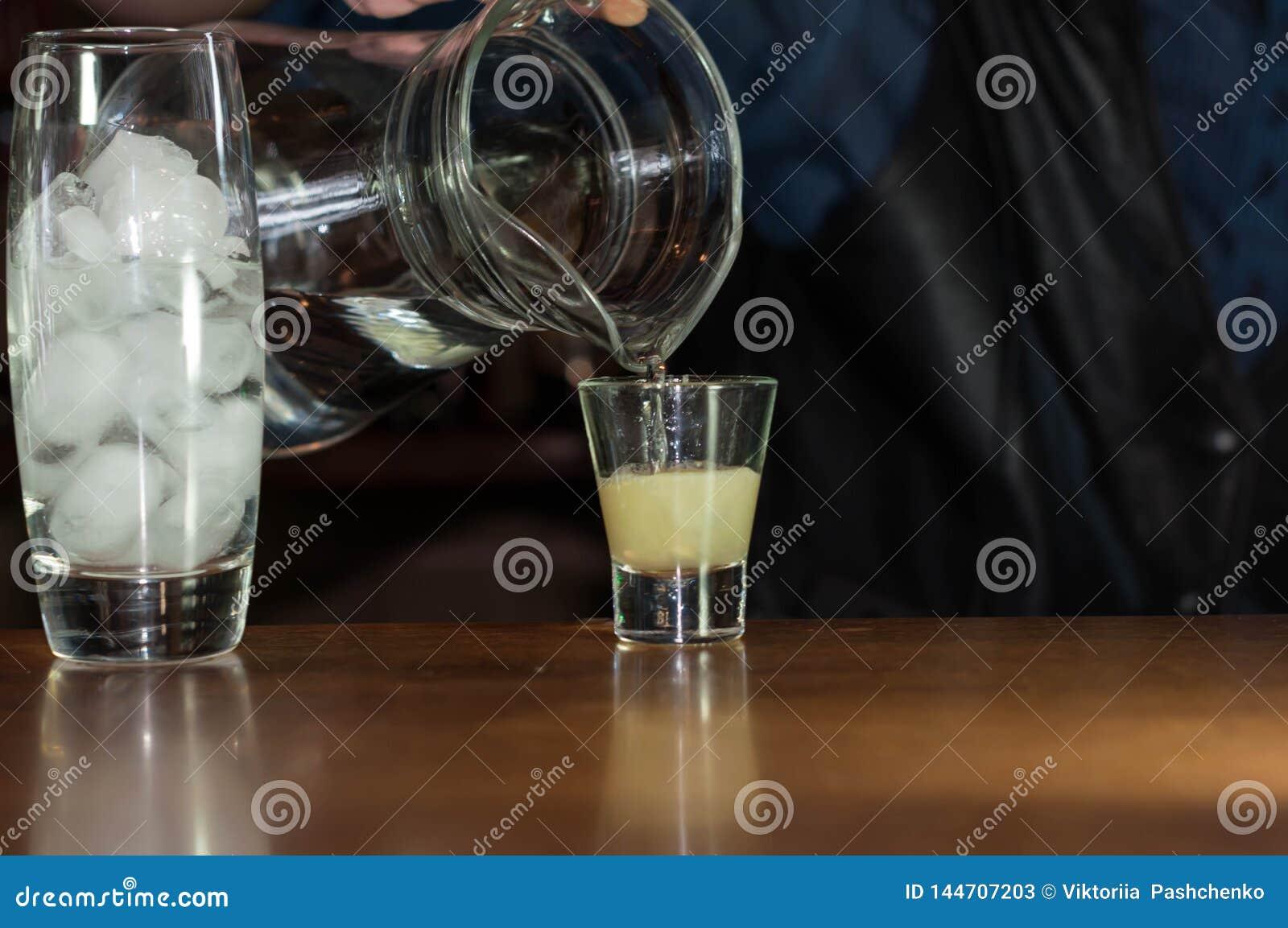 Barman à la soude se renversante de compteur de la cruche dans le verre avec du jus
