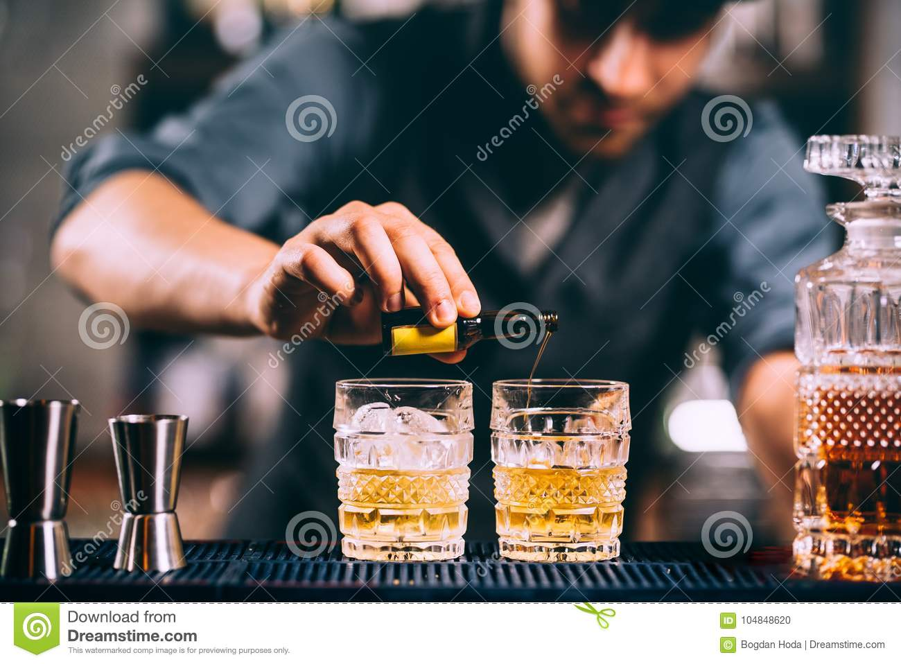 Barman adding cocktail ingredients on whiskey cocktails at the bar
