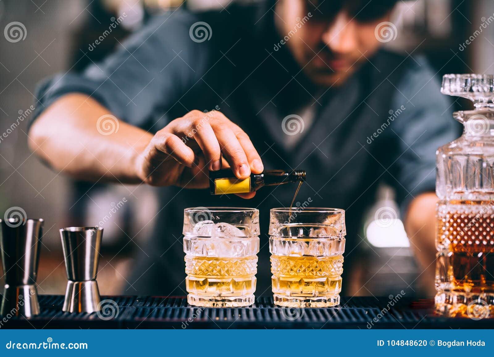 Barman ajoutant des ingrédients de cocktail sur des cocktails de whiskey à la barre