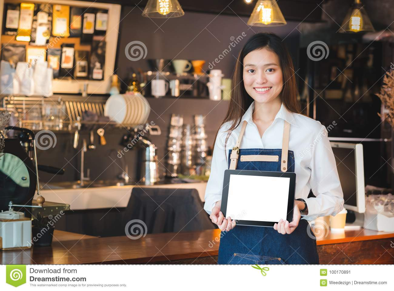 Barman asiatique de sourire de femme tenant le calcul vide de comprimé dans le fron