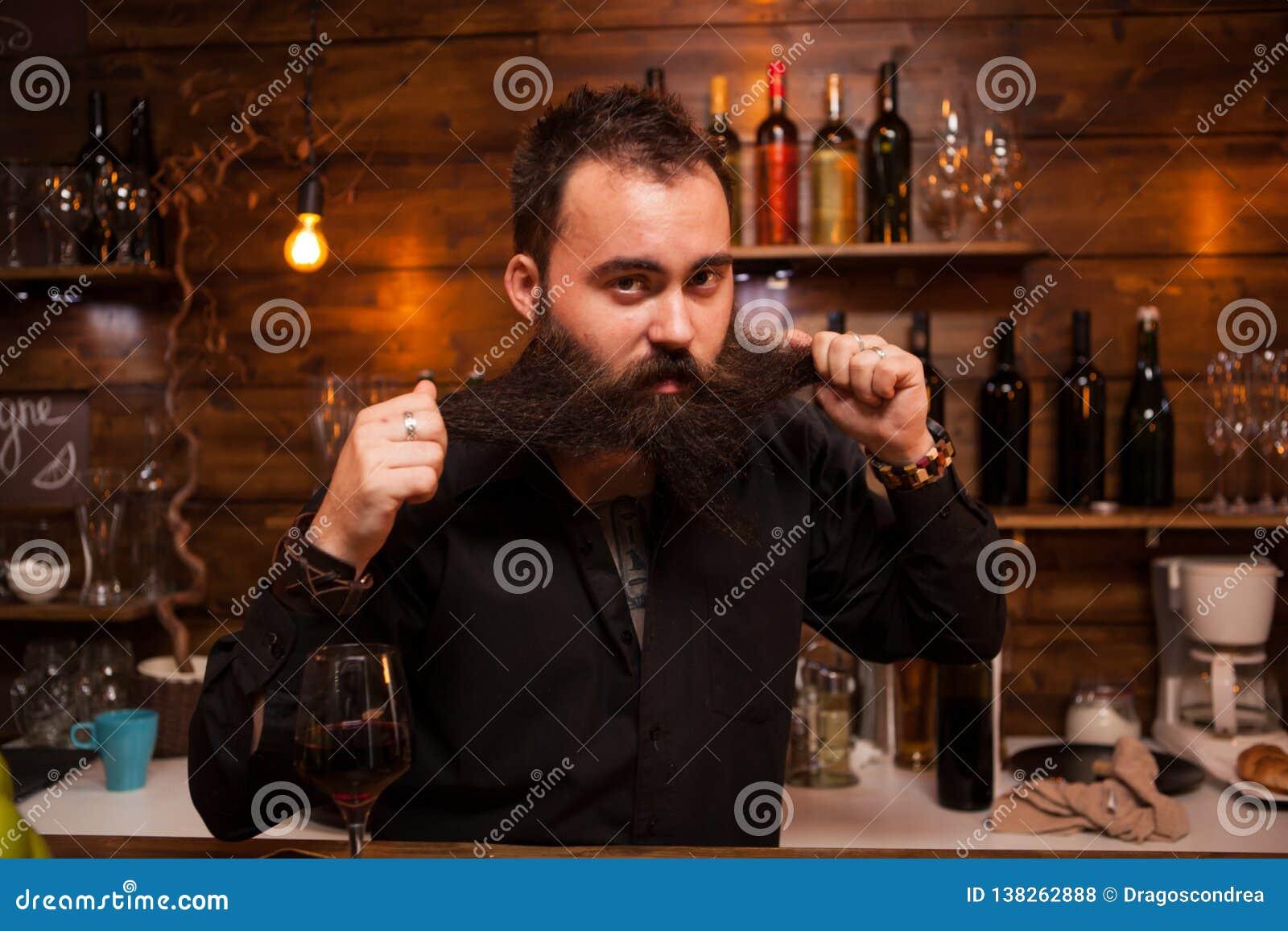 Barman atrativo que joga com sua barba longa atrás do contador