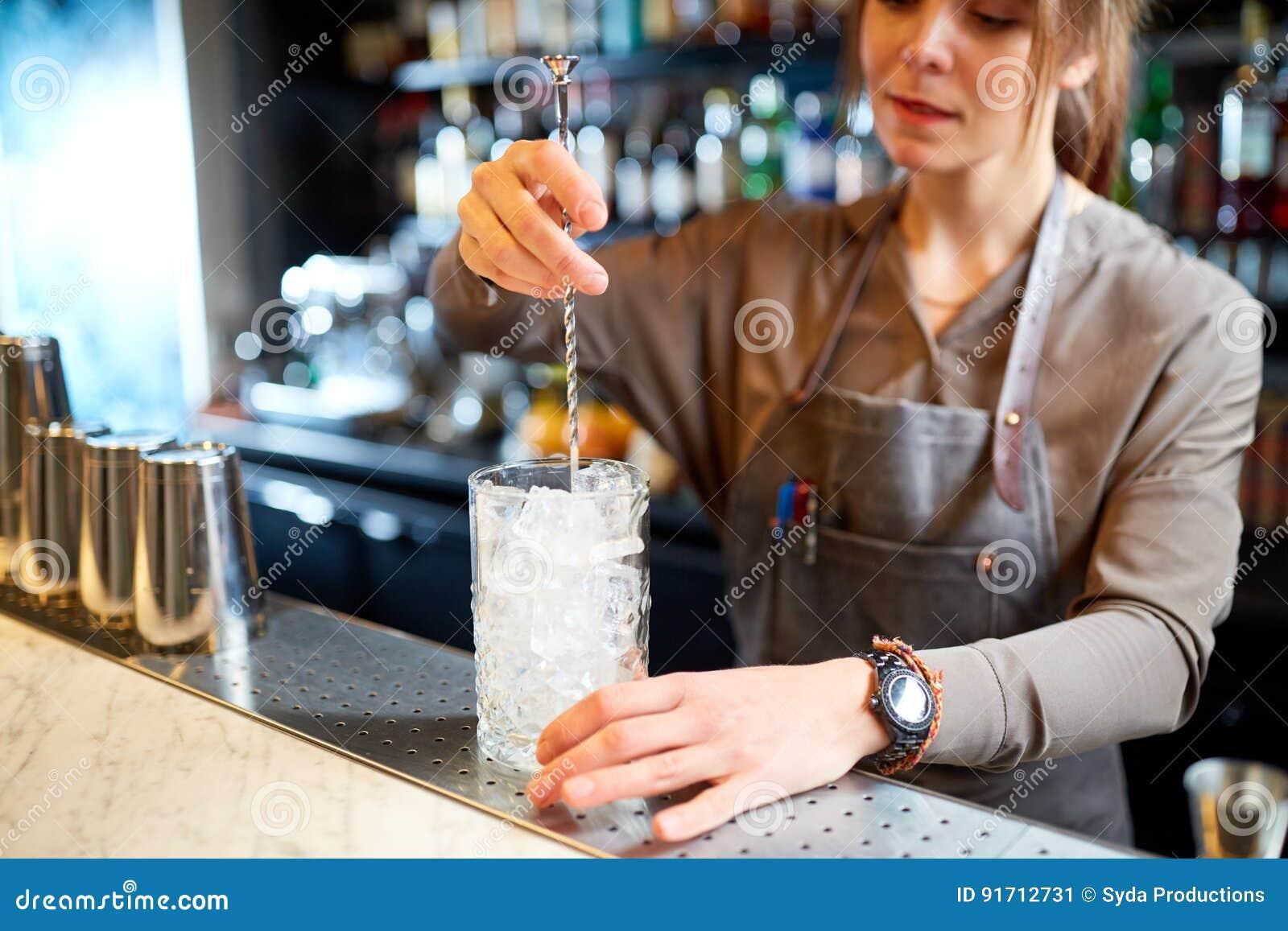 L Agitateur barman avec l'agitateur et le verre de cocktail à la barre image