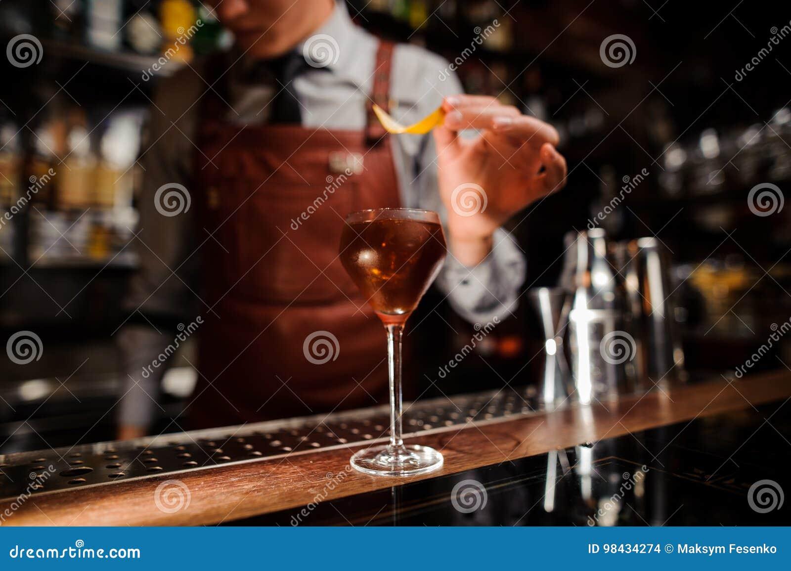 Barman avec la peau en verre et de citron préparant le cocktail à la barre