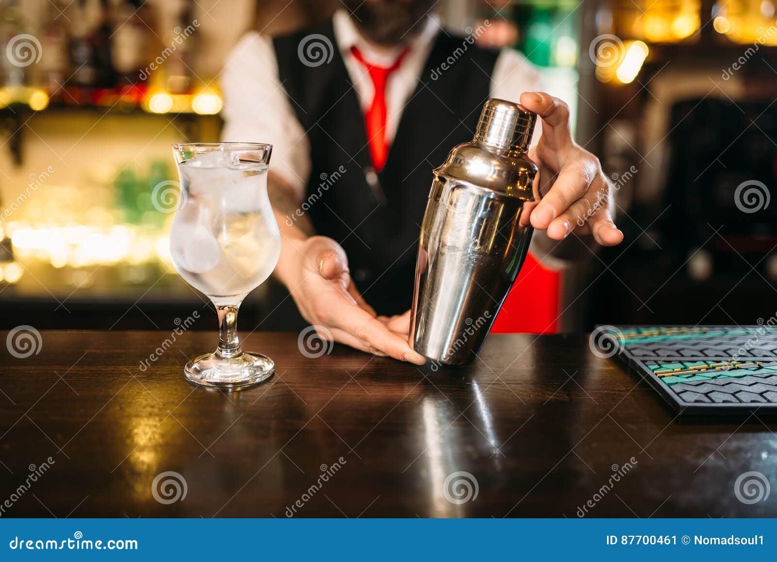 Barman avec le dispositif trembleur derrière un compteur de barre