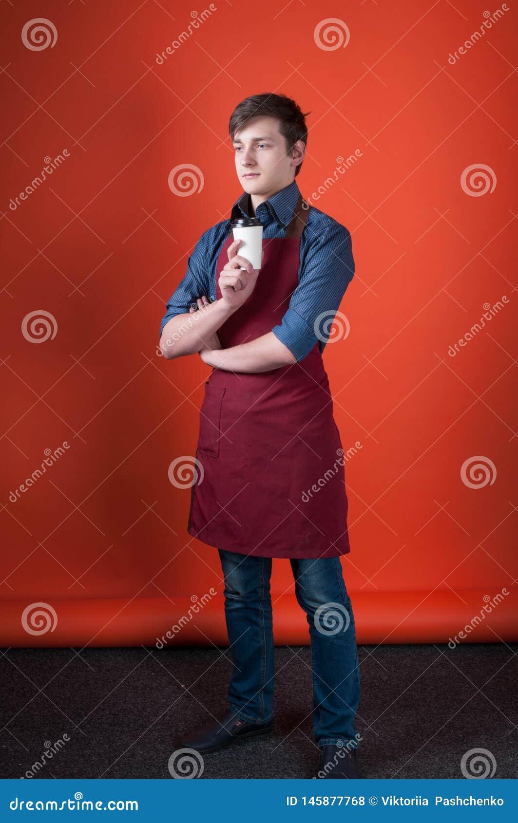 Barman avec les cheveux foncés dans le tablier de Bourgogne tenant la tasse de papier avec du café et regardant loin le studio de