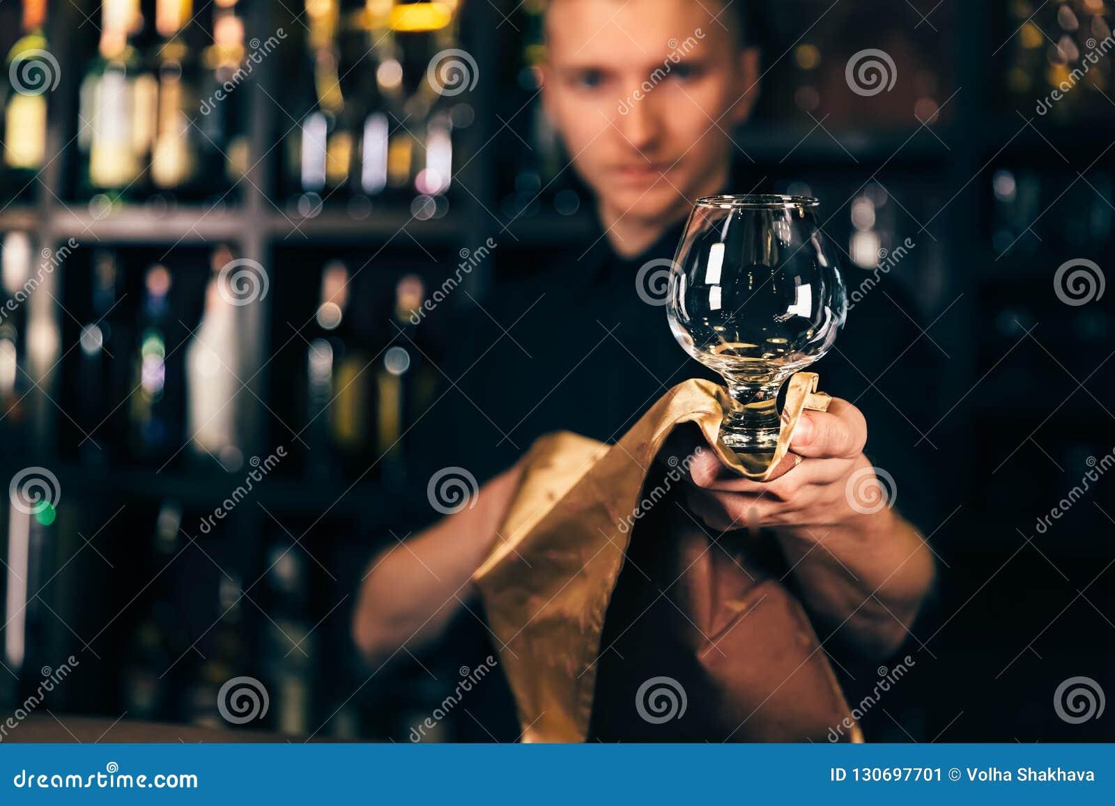 Barman czyści szkło z płótnem przy baru kontuaru tłem Barman czyści szkło na barze