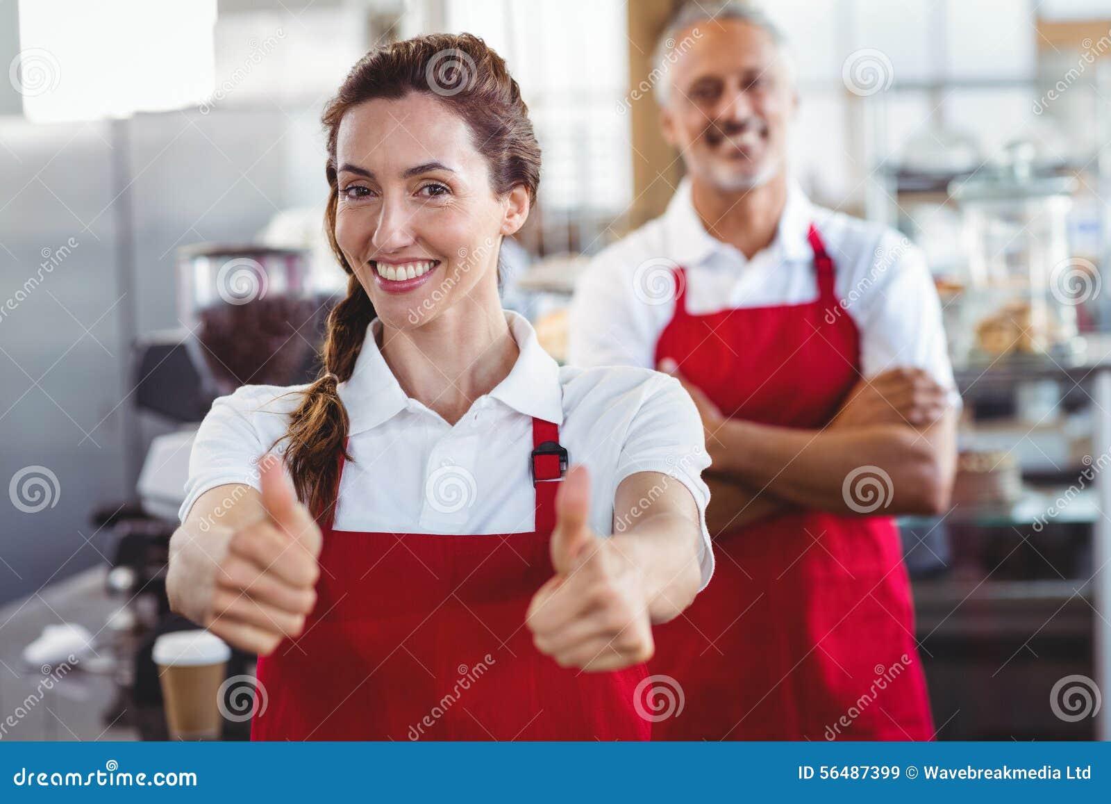 Barman de sourire faisant des gestes des pouces avec le collègue derrière