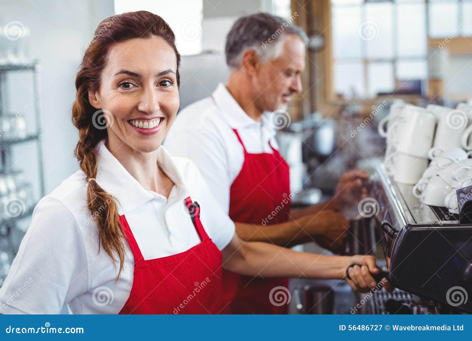 Barman de sourire utilisant la machine de café avec le collègue derrière