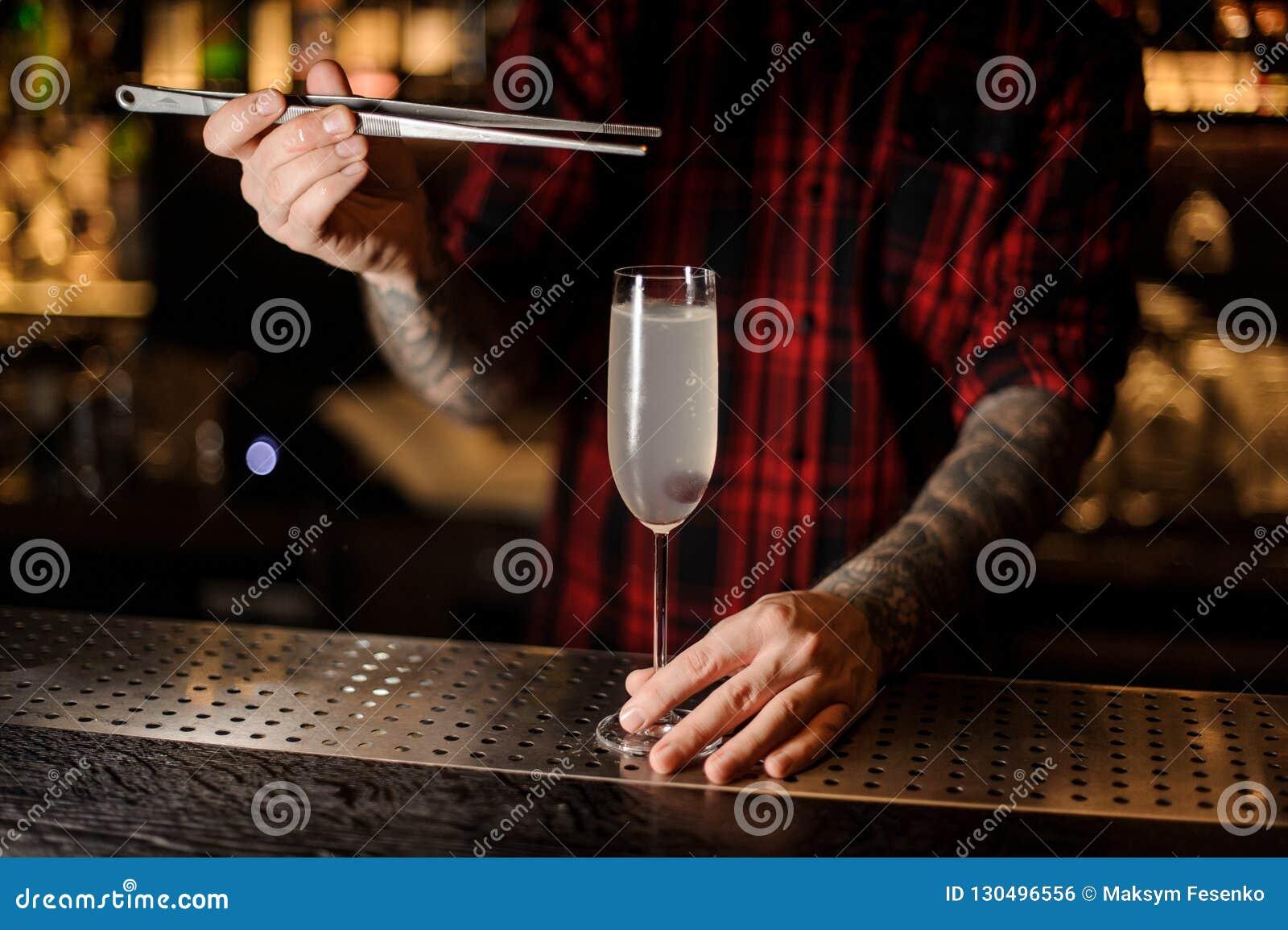 Barman die bes toevoegen aan een heerlijke cocktail het Frans 75