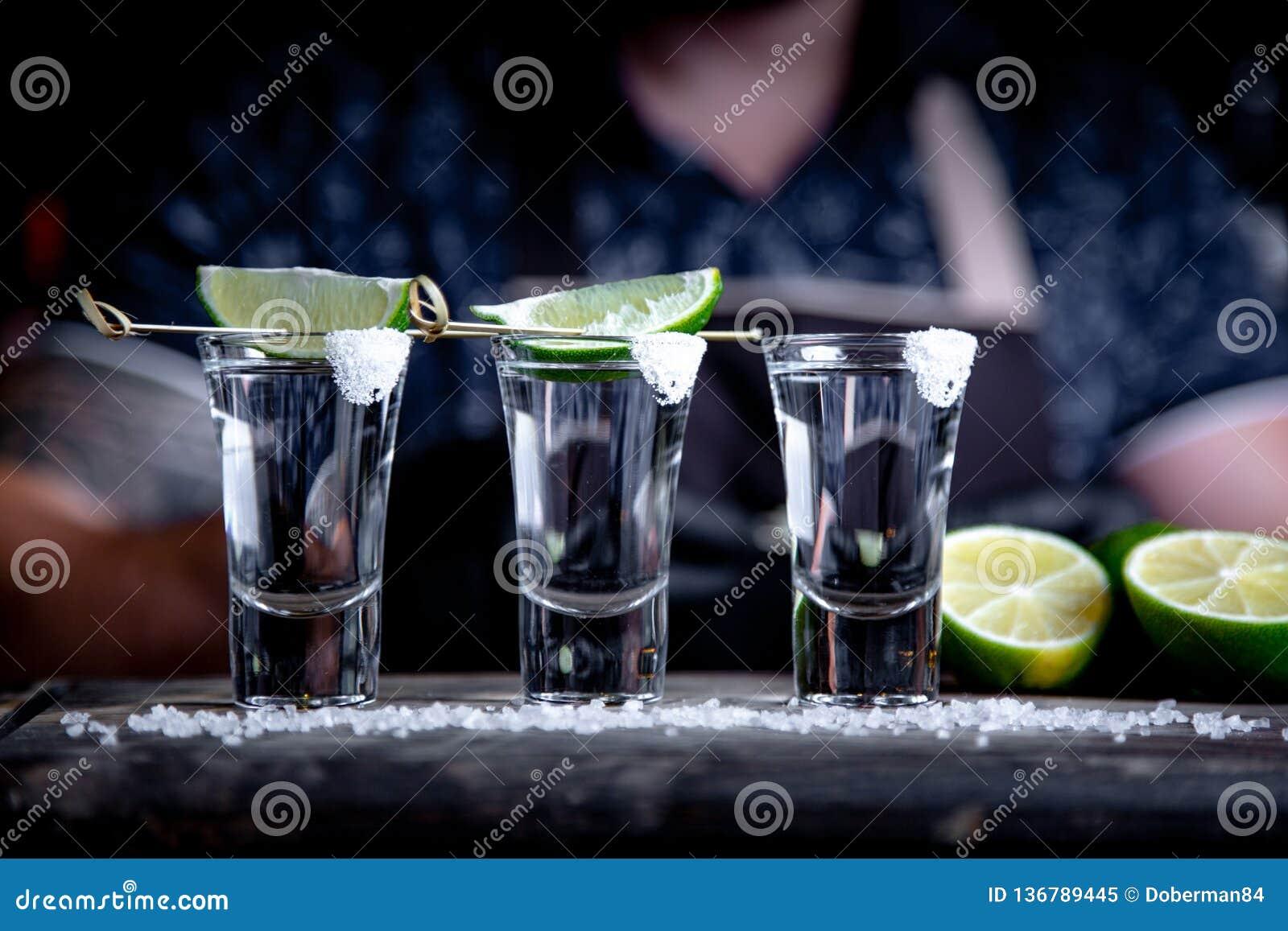 Barman die harde geest gieten in kleine glazen zoals alcoholische schoten van tequila of sterke drank