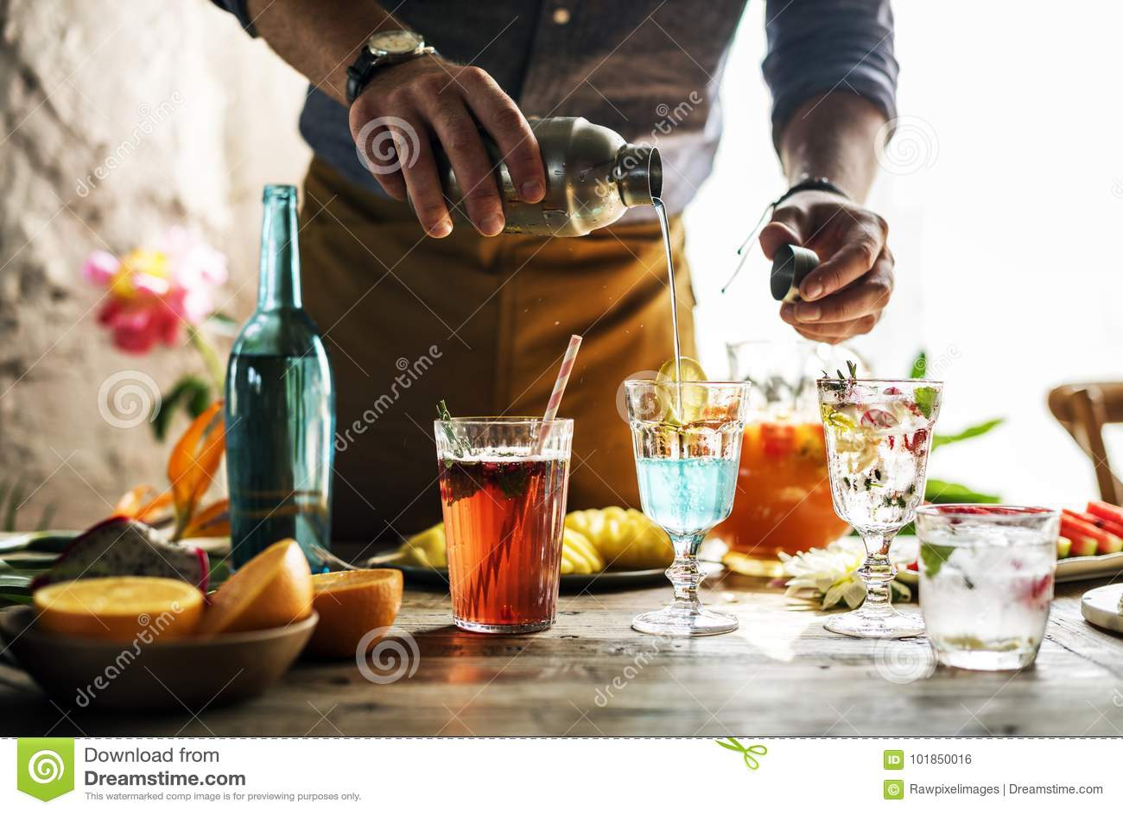 Barman die kleurrijke cocktails mengen