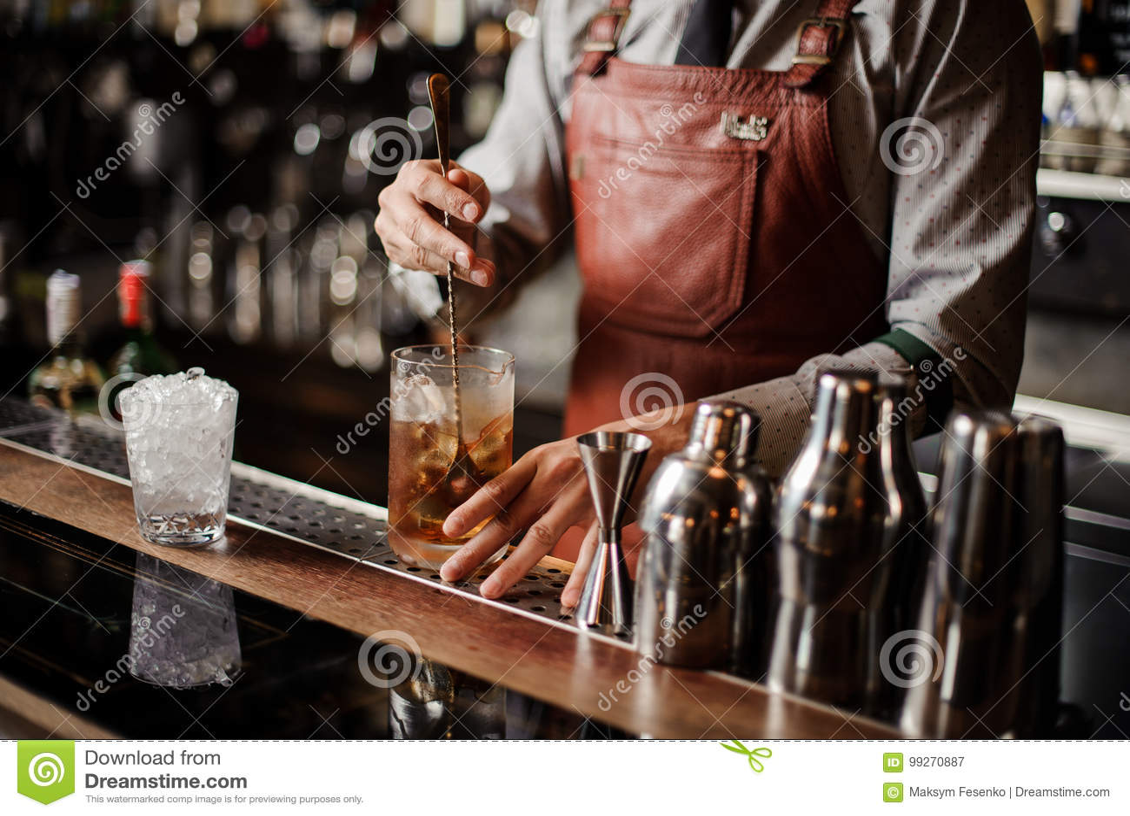 Barman die uit Cocktailglas koelen die ijs mengen met een lepel