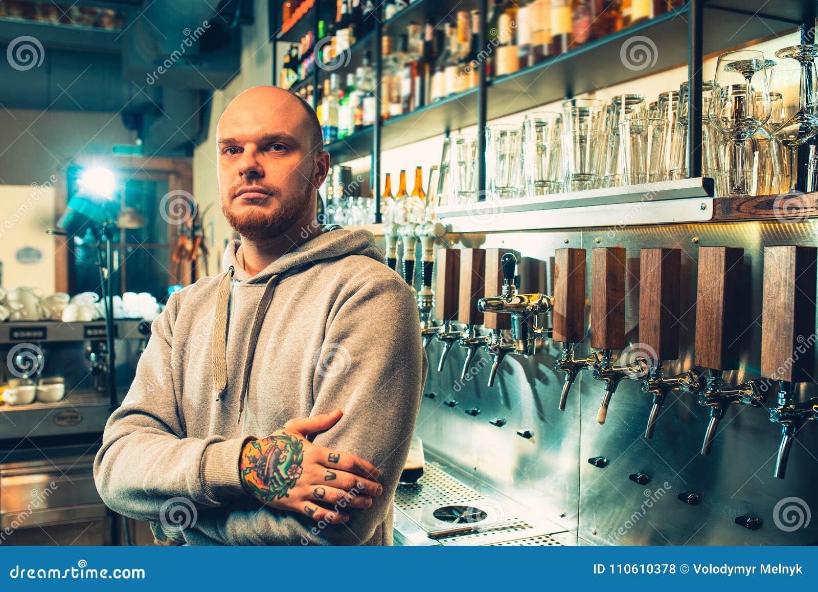 Barman in een bar dichtbij bierkranen