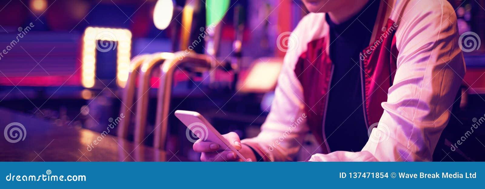 Barman féminin à l aide du téléphone portable au compteur de barre