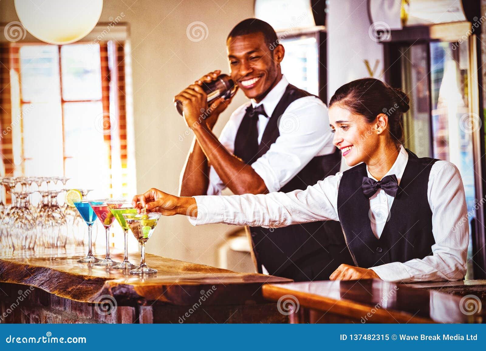 Barman féminin garnissant le cocktail avec l olive