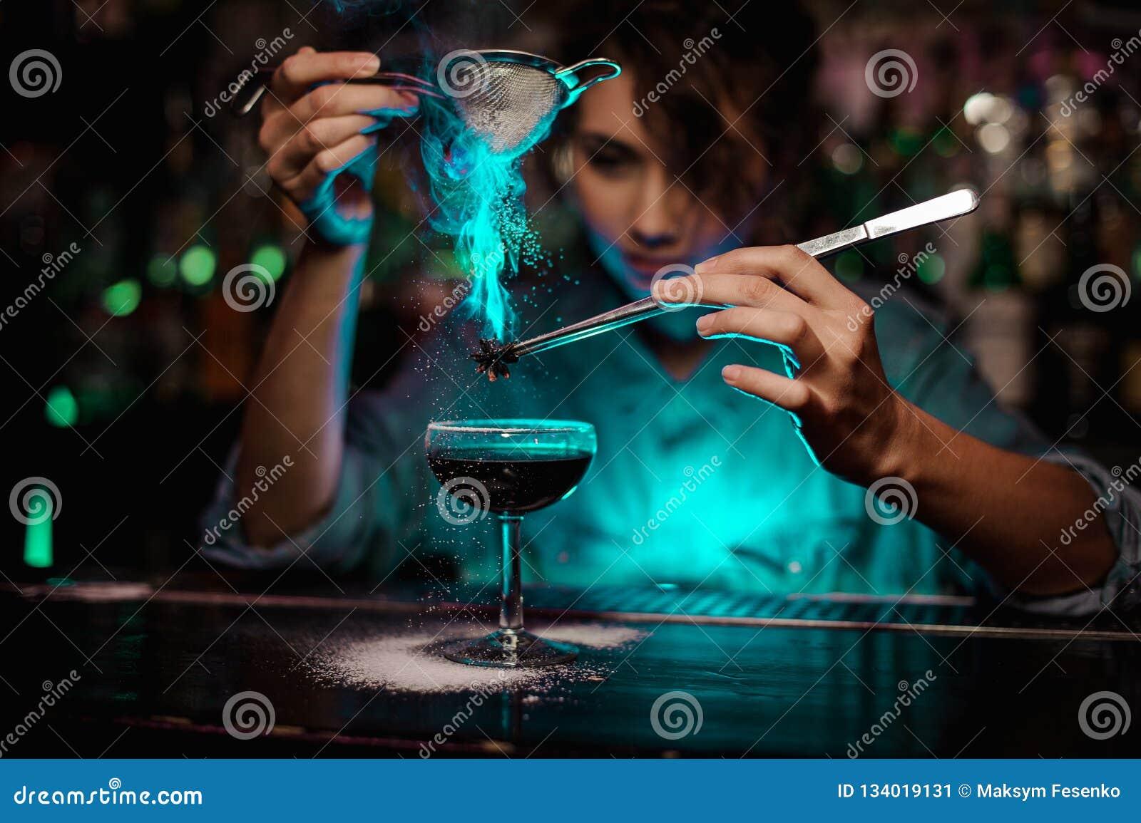 Barman féminin versant sur le cocktail brun et sur un badian flambé sur des brucelles un sucre en poudre dans le feu vert