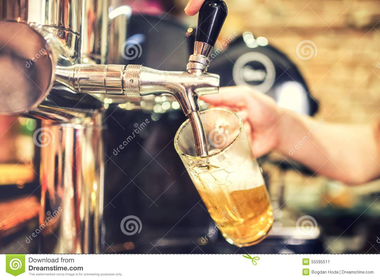 Barman hand at beer tap pouring a draught lager beer serving in a restaurant