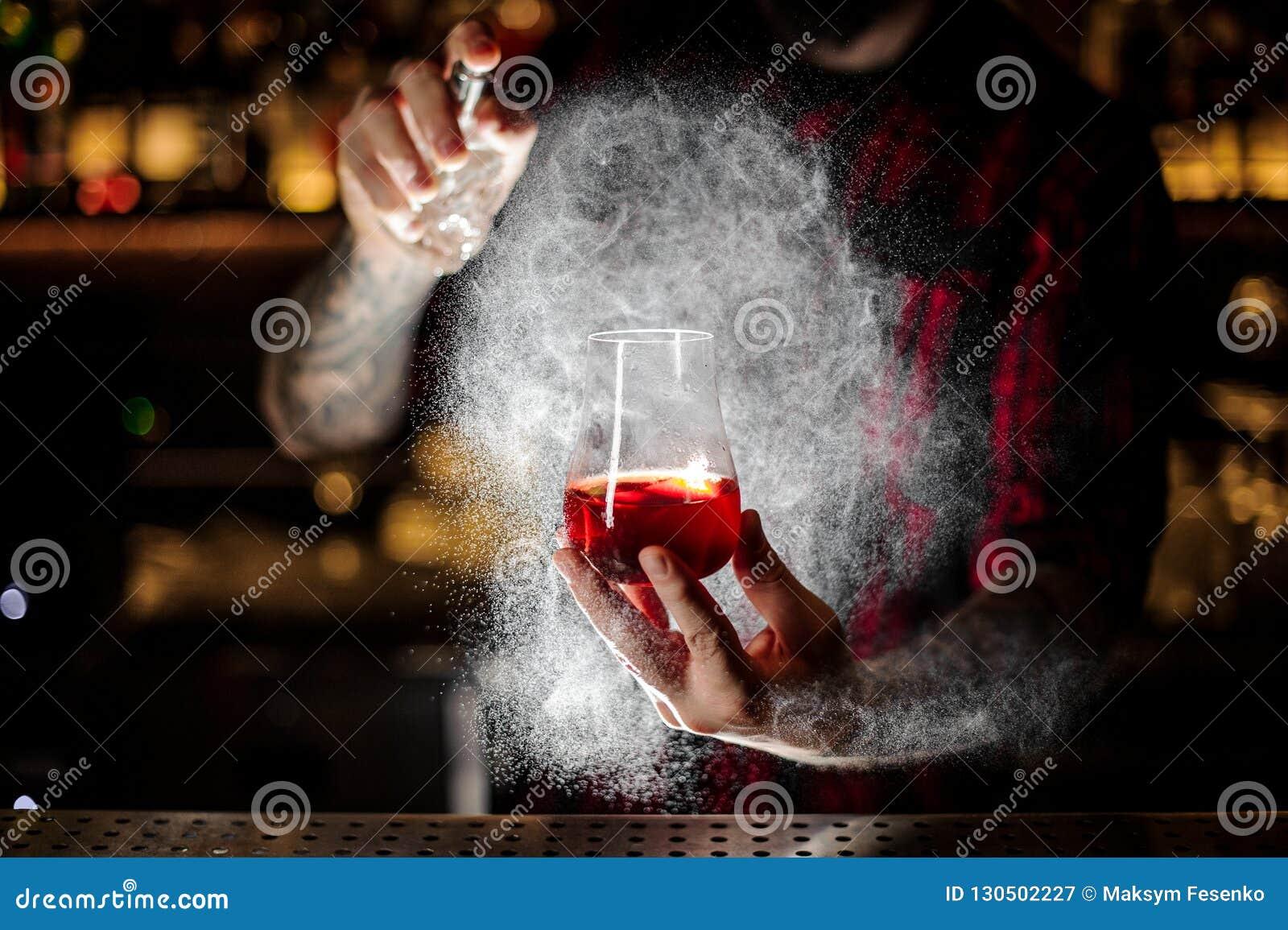 Barman het bespuiten op de Sazerac-cocktail met oranje schil