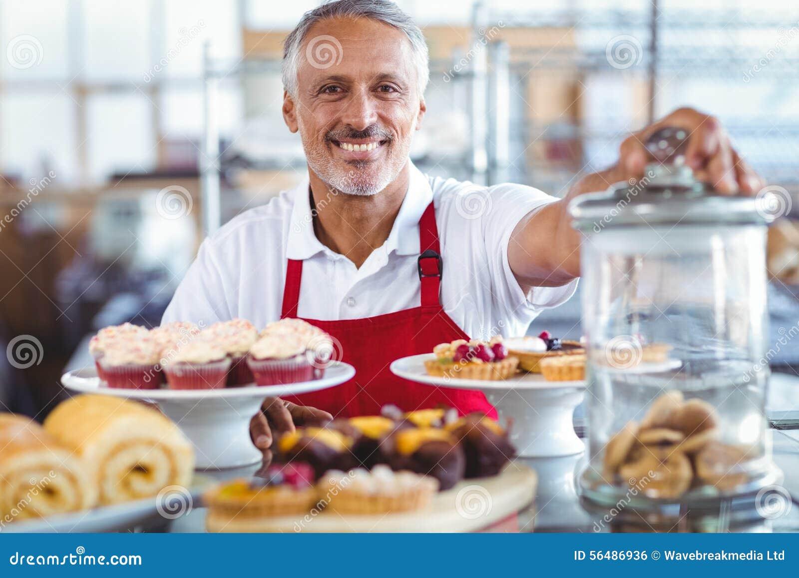 Barman heureux souriant à l appareil-photo derrière des plats des gâteaux