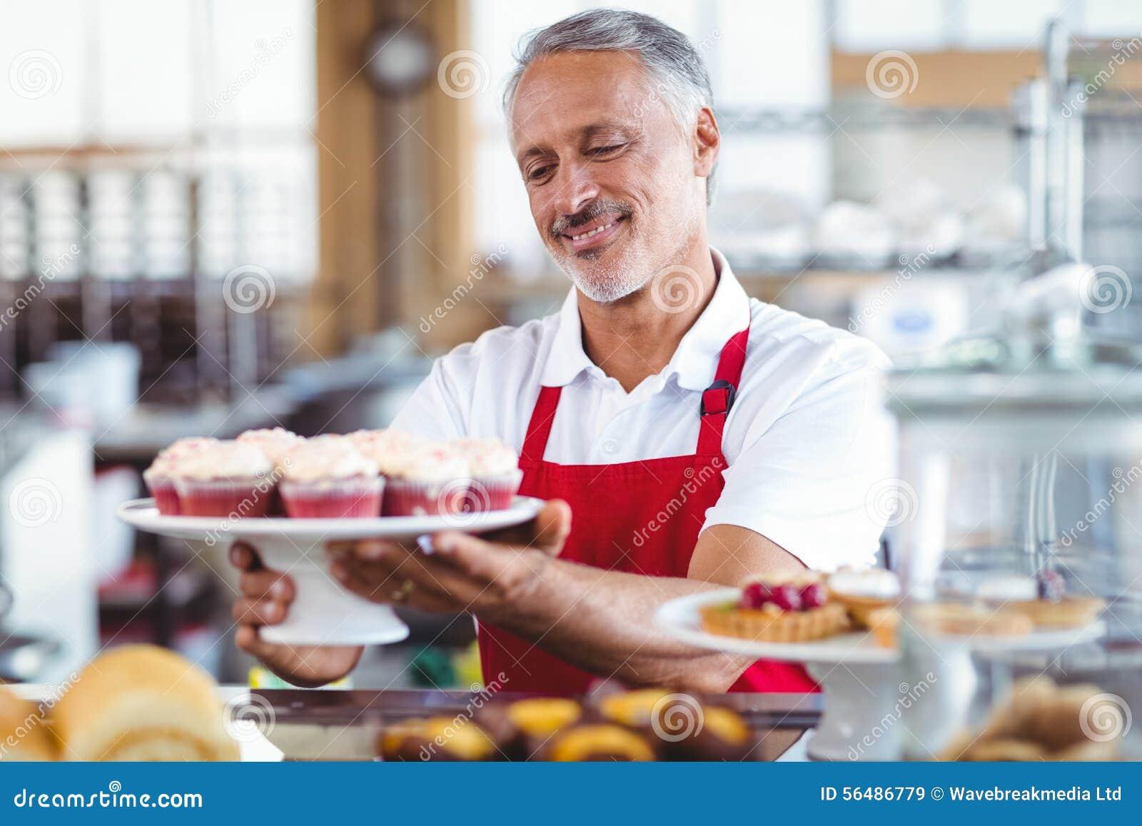 Barman heureux tenant un plat des petits gâteaux