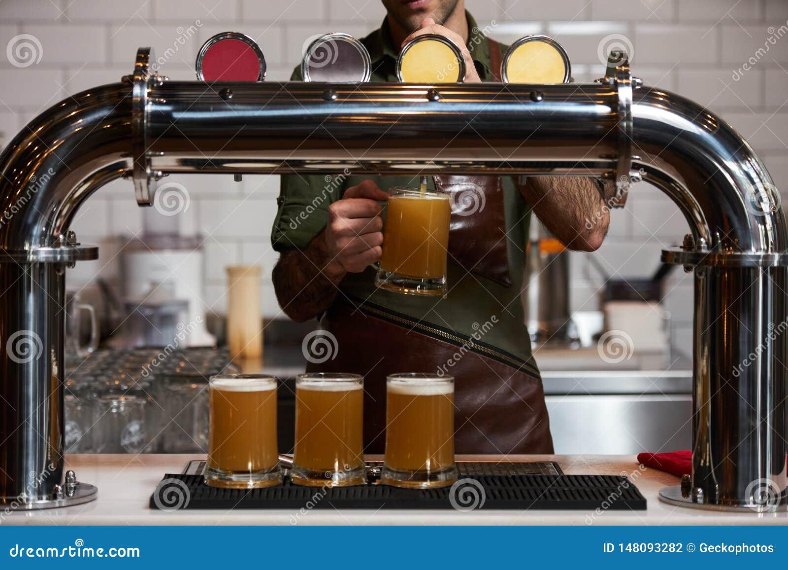 Barman nalewa świeżego piwo w piwnego szkło przy baru kontuarem, w górę
