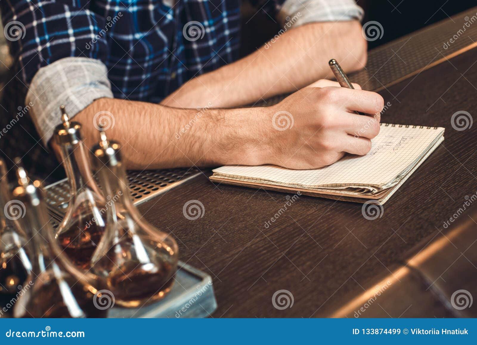 Barman novo que inclina-se no close-up do inventário da escrita do contador da barra