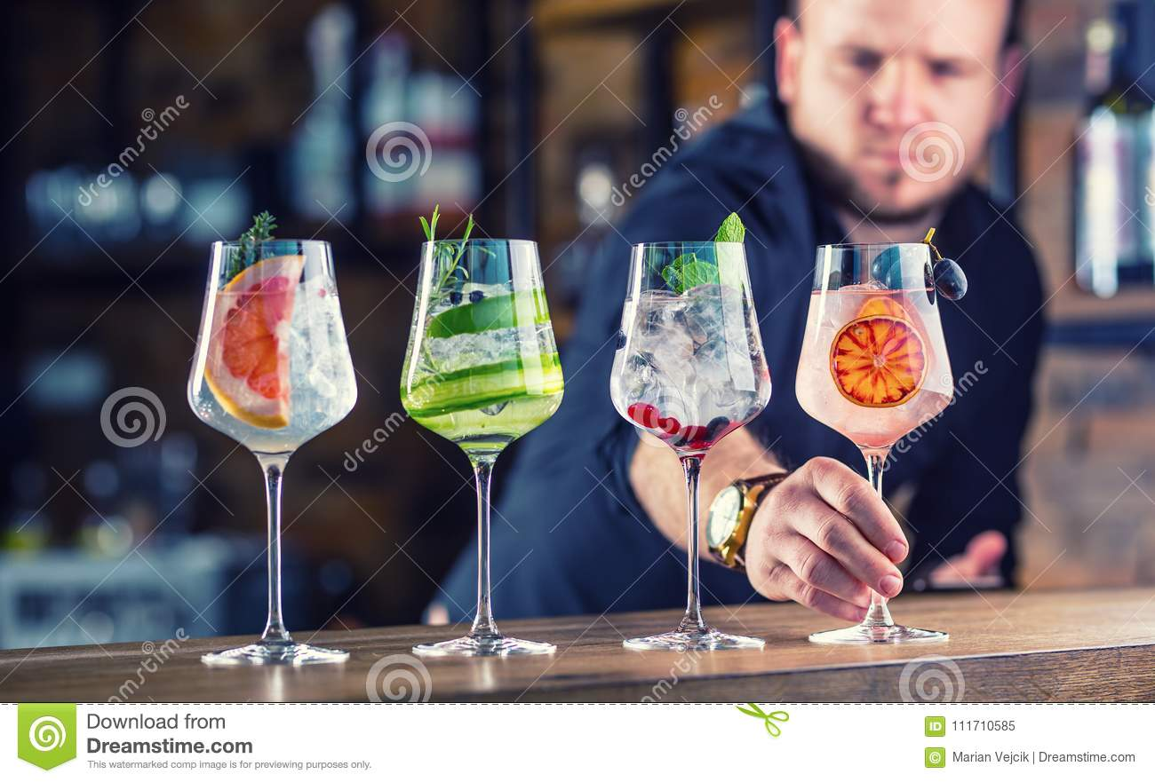 Barman in pub or restaurant preparing a gin tonic cocktail drin