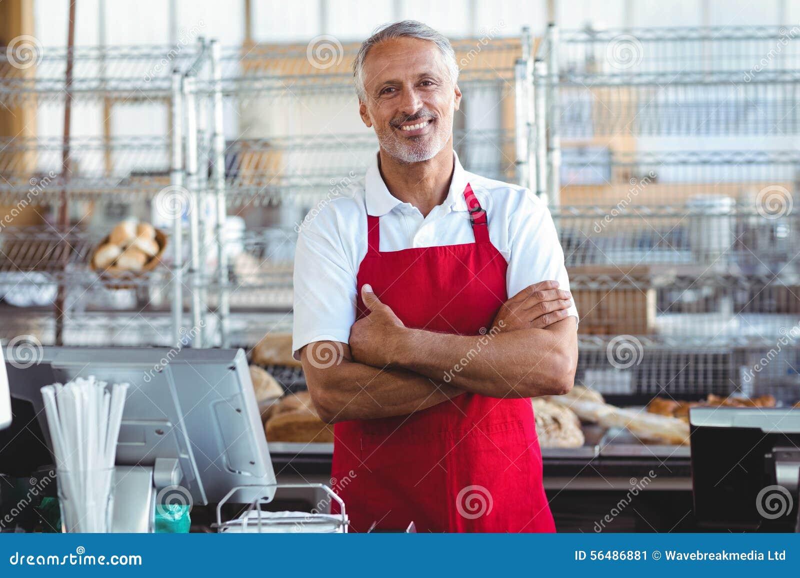 Barman souriant à l appareil-photo avec des bras croisés