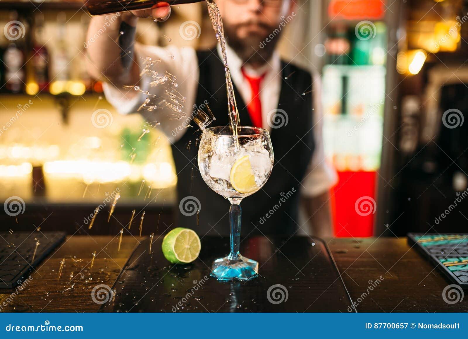 Barman versant la boisson alcoolisée en verre