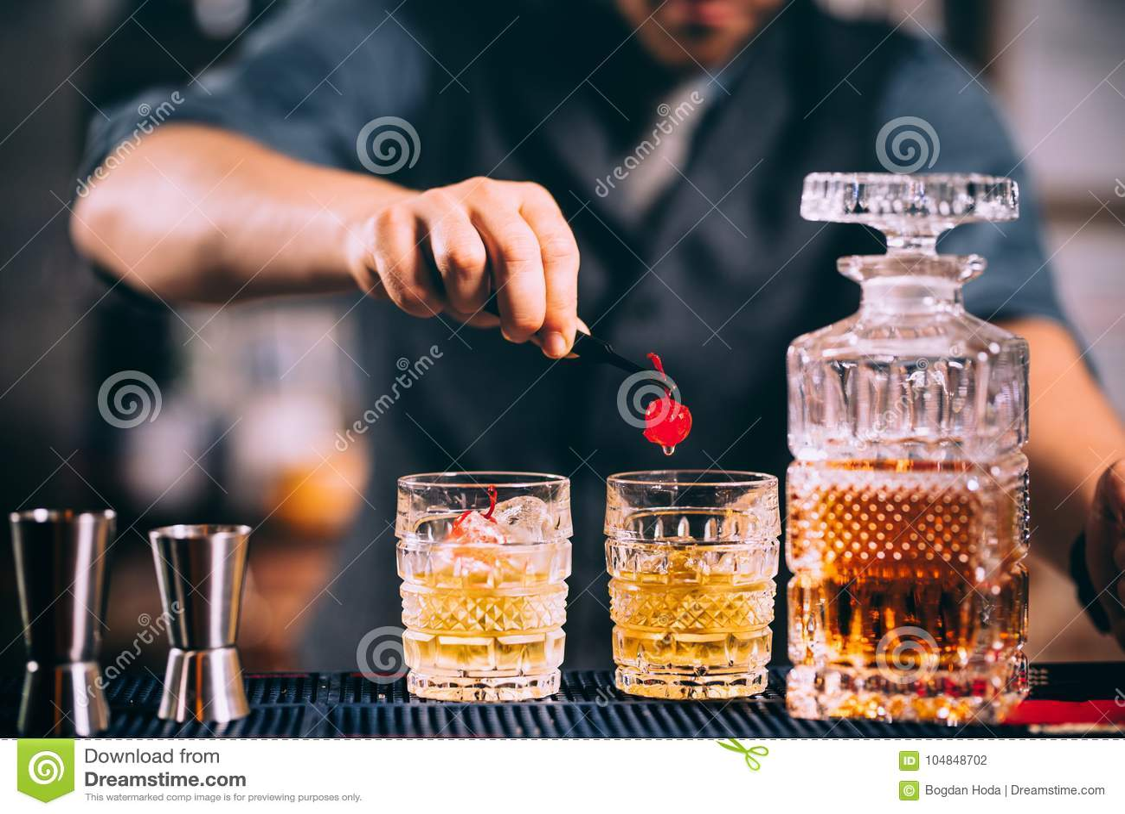 Barman voorbereidingen treffende en voerende van de kristalwhisky glazen voor alcoholische dranken