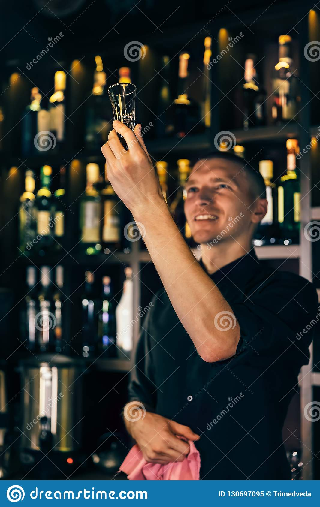 Barman watches a crystal glass. The bartender cleaning the glass on the bar