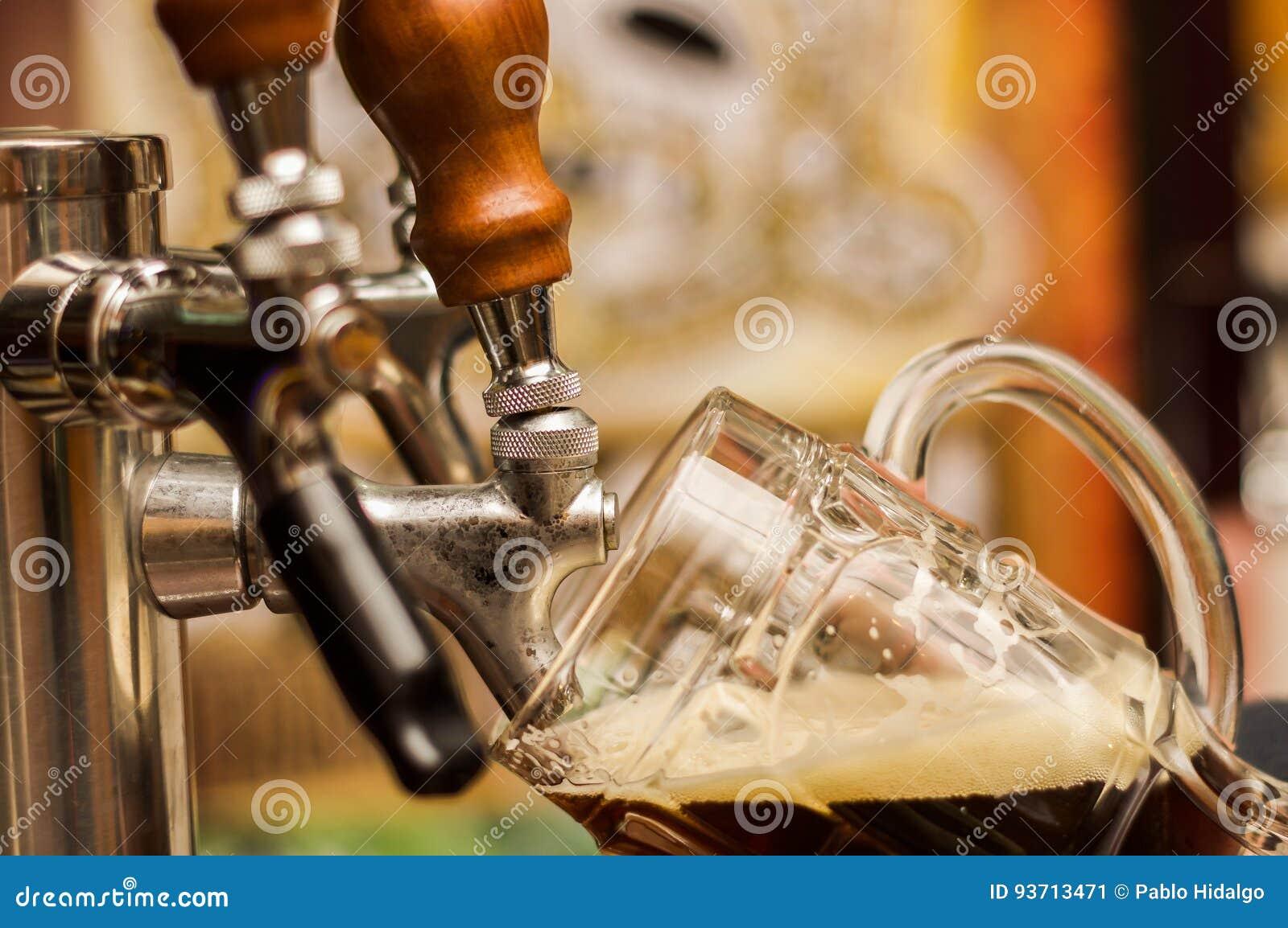 Barman wypełnia w górę zmroku z rzemiosła piwem pół kwarty szkło